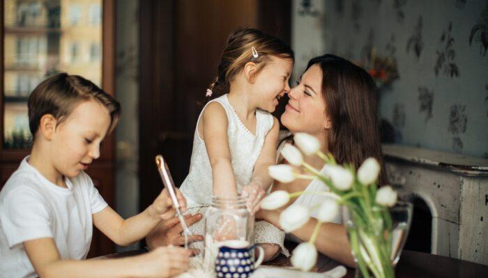 Mor og hendes to børn sidder i køkken