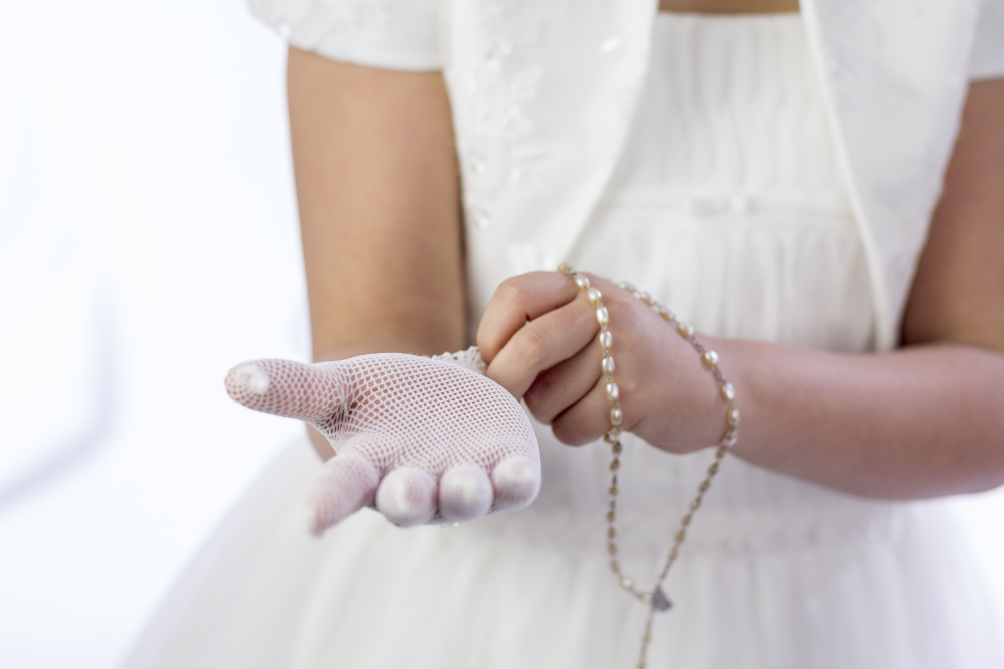 A young girl with rosary putting on her gloves for her First Holy Communion
